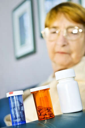 Elderly woman looking at pill bottles with medication Stock fotó