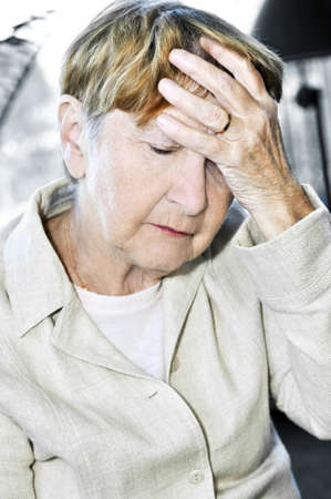 Sad senior woman holding her hand over forehead