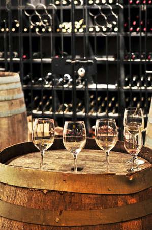 Rij van wijn glazen op vat in de wijn kelder