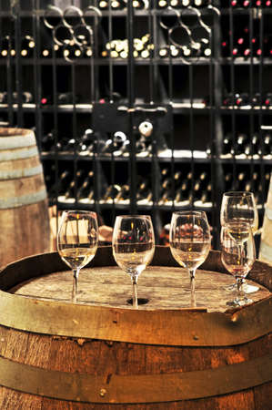 winemaker: Row of wine glasses on barrel in winery cellar Stock Photo
