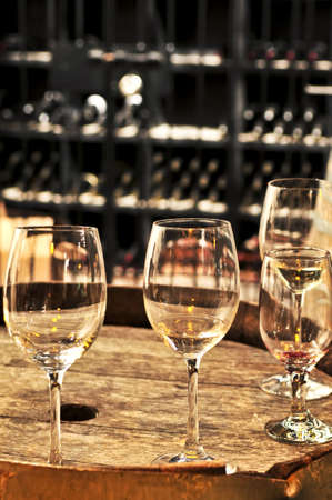 white wine: Row of wine glasses on barrel in winery cellar Stock Photo