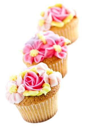 cake decorating: Row of tasty cupcakes with icing flowers