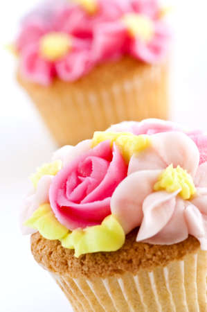 Row of tasty cupcakes with icing flowers photo