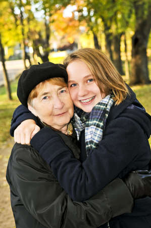 Teen granddaughter hugging grandmother in autumn park Stock Photo - 4687828