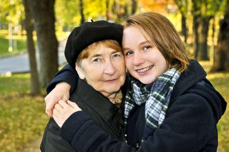 Teen granddaughter hugging grandmother in autumn park Stock Photo - 4687995