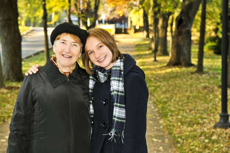 Teen granddaughter walking with grandmother in autumn park photo