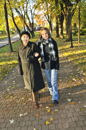 Teen granddaughter walking with grandmother in autumn park Stock Photo - 4687992