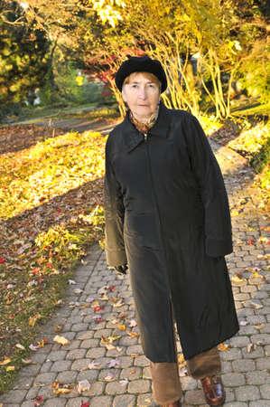 Senior woman walking alone in fall park photo