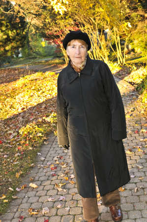 Senior woman walking alone in fall park Stock Photo - 4688004