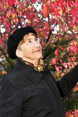 Senior woman looking up in fall park photo