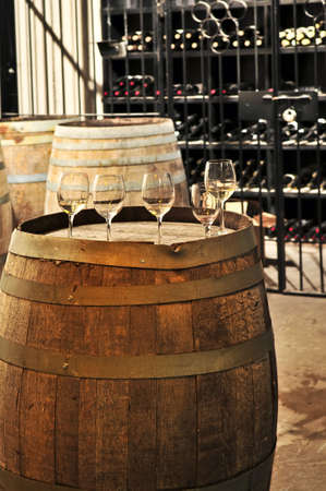 casks: Row of wine glasses on barrel in winery cellar Stock Photo