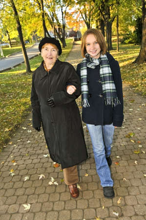 Teen granddaughter walking with grandmother in autumn park Stock Photo - 4710013