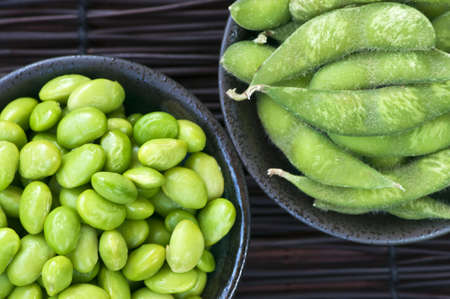 Edamame soy beans shelled and with pods in bowls photo