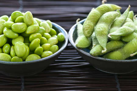 shucked: Edamame soy beans shelled and with pods in bowls