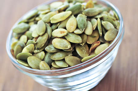 Pumpkin seeds close up in glass bowl photo