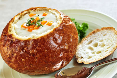 Lunch of soup served in baked round bread bowl photo