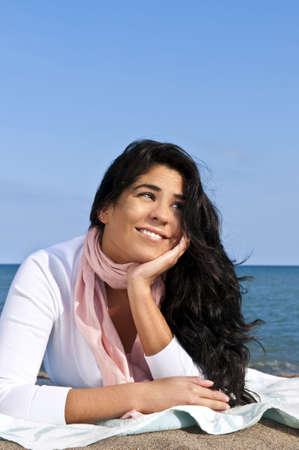 native american girl: Portrait of beautiful smiling native american girl laying at beach Stock Photo