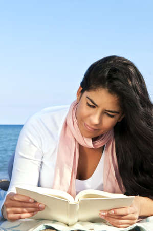 Portrait of beautiful smiling native american girl reading book at beach photo