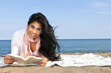 American Indian: Retrato de la hermosa muchacha sonriente nativo americano libro de lectura en la playa