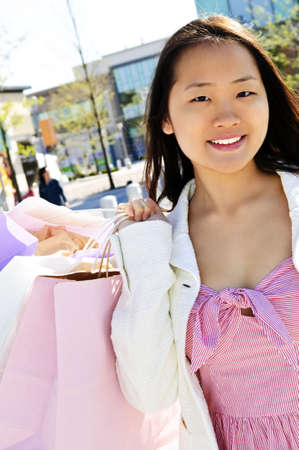 Young korean woman with shopping bags at outdoor mall photo