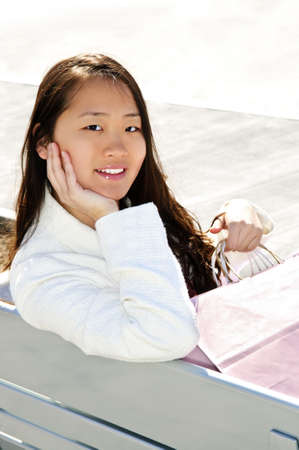 Young korean woman with shopping bags at outdoor mall sitting on bench Stock Photo - 4900508