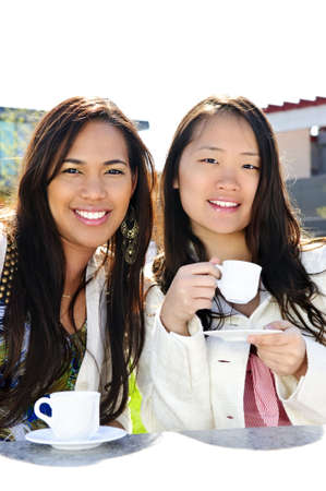 Two girl friends sitting and having drinks at outdoor mall Stock Photo - 4900471