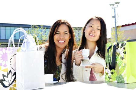 Twee vriendinnen zitten en met drank op outdoor winkelcentrum met boodschappentassen