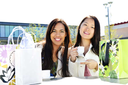 Two girl friends sitting and having drinks at outdoor mall with shopping bags