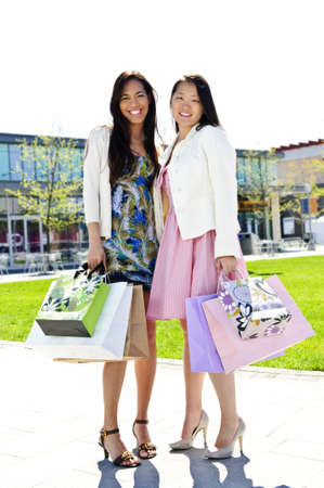 Two girl friends standing at outdoor mall with shopping bags photo