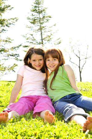 草の上に座って幸せな女の子の肖像画