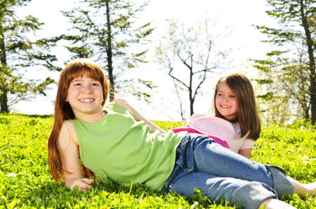Portrait of happy girls sitting on grass