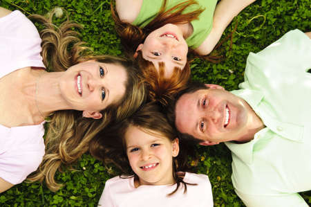 elevated view: Portrait of happy family laying  on grass looking up heads together