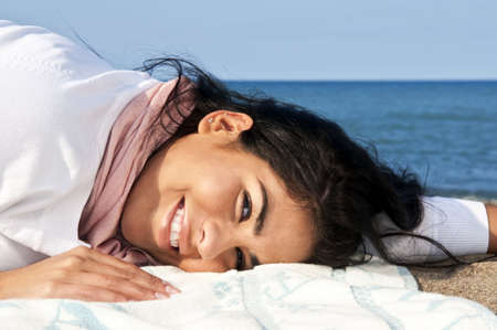 aboriginal woman: Portrait of beautiful smiling native american girl laying at beach Stock Photo