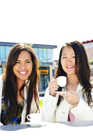 Two girl friends sitting and having drinks at outdoor mall photo