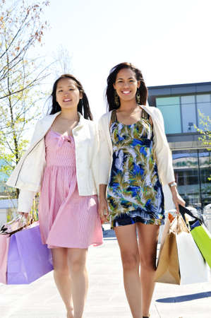 Two young girl friends holding shopping bags at mall photo