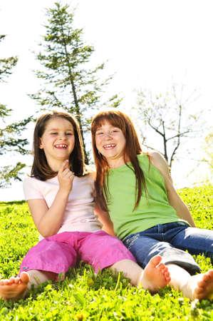 Portret van gelukkige meisjes zitten op gras Stockfoto