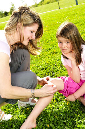 bandage: Portrait of mother giving first aid to daughters cut knee Stock Photo