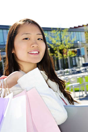 Young korean woman with shopping bags at outdoor mall sitting on bench photo