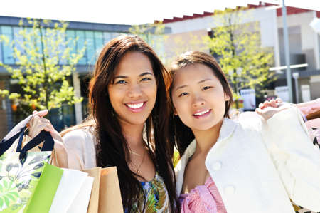 Two young girl friends holding shopping bags at mall Stock Photo - 4943221
