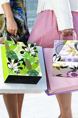 Two young girl friends holding shopping bags at mall Stock Photo - 4943827