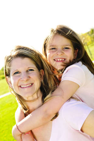 Portrait of happy mother giving piggyback ride to child photo
