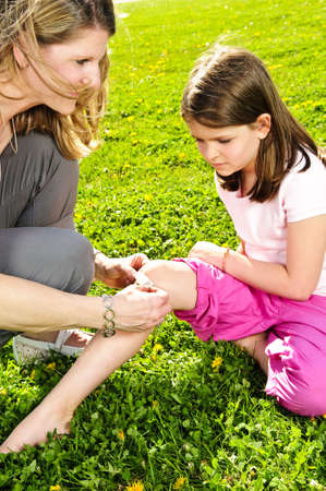 de rodillas: Retrato de la madre dando los primeros auxilios a las hijas de corte de rodilla