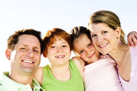 Portrait of happy family of four hugging and smiling Stock Photo - 5010647