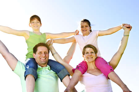 Portrait of happy parents giving children shoulder rides Stok Fotoğraf