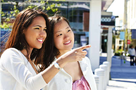 Two young girlfriends at outdoor mall pointing photo