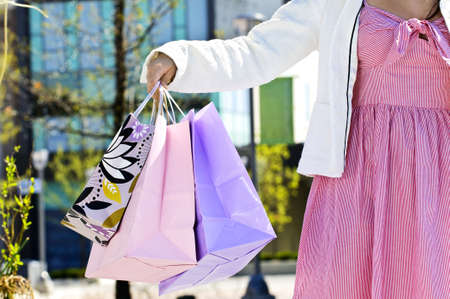 plaza of arms: Young girl holding shopping bags at mall Stock Photo
