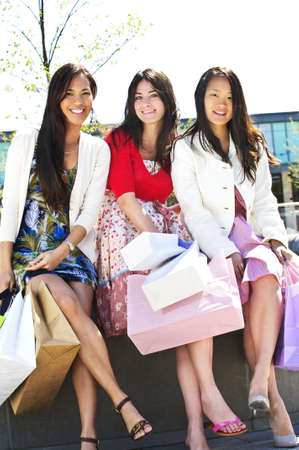 spree: Group of young girl friends holding shopping bags at mall Stock Photo