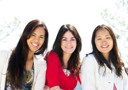 Group of three diverse young girlfriends smiling photo
