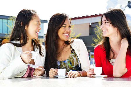 Group of girl friends sitting and having drinks at outdoor cafe photo