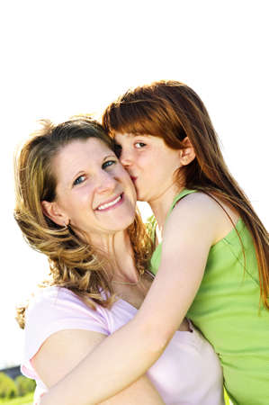 Portrait of happy child hugging and kissing her mother